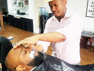 Shown is participating barber Ken Moore with client Ronnie King