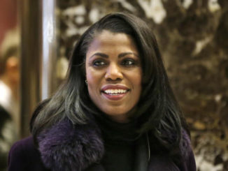 Omarosa Manigault smiles at reporters as she walks through the lobby of Trump Tower in New York, Tuesday, Dec. 13, 2016. (AP Photo/Seth Wenig)