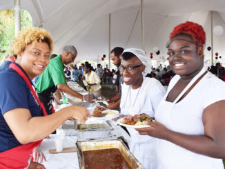 Shown serving gourmet fare is celebrity server State Representative Tracie Davis with MOAS participants