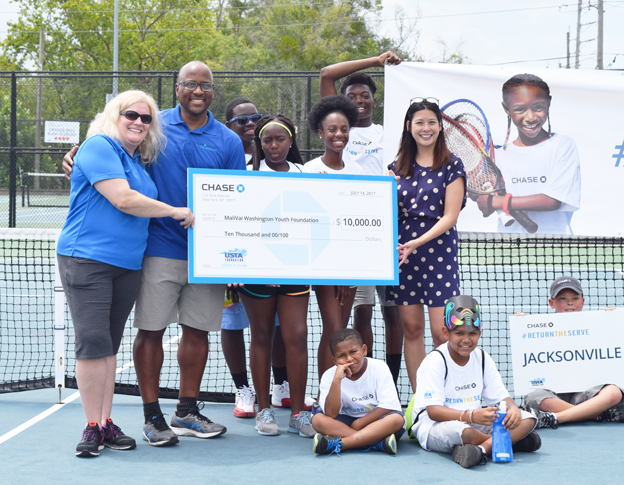 Pictured showcasing the awarded check left to right is Jackie Materasso, USTA Foundation, MaliVai Washington, Founder, Nyreon Shuman, Mauricia Brown, Tiah Thomas-Jacobs and Traveon Harris. Seated L to R: Trey Scott, Christian Thomas and Isaiah Pickett.