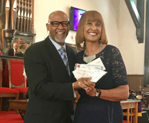 Shown is Mt. Zion Allenites president Olivia Young presenting the check to Reverend Pearce Ewing, Sr.
