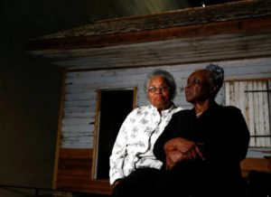 Emily Meggett, left, and Isabell Meggett Lucas sit together at the National Museum of African American History in Washington, Tuesday, April 11, 2017, in front of a slave cabin on display. Lucas was born in the two-room wood cabin that dates to the 1850's. It is believed to be one of the oldest preserved slave cabins in the U.S.