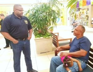 Pictured is Sheriff Darryl Daniels talking  with mall shopper Jerome Mayweather.