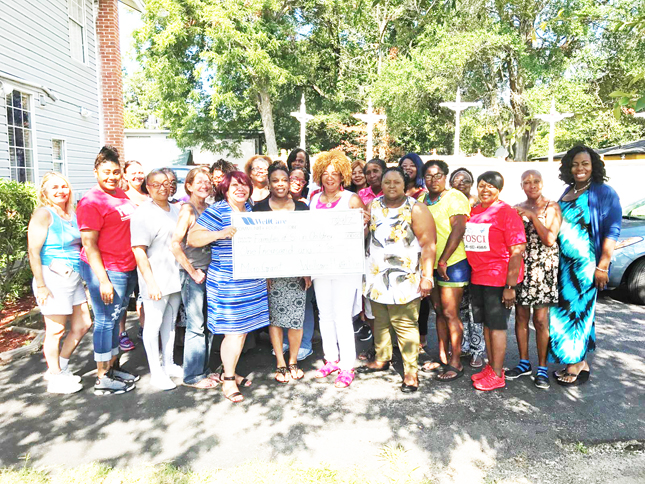 Shown in the photo accepting the Wellcare grant is Beverly McClain, her staff and workshop attendees.