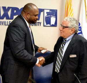 New Jaxport CEO gets a congratulatory handshake from Board Chairman John Citrano.