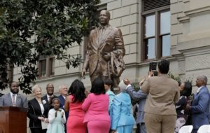"""A statue paying tribute to civil rights leader Martin Luther King Jr. is unveiled by Georgia Gov. Nathan Deal, center left, members of the King family and others on the state Capitol grounds in Atlanta, Monday, Aug. 28, 2017. The statue's unveiling Monday came more than three years after Georgia lawmakers endorsed the project. A replica of the nation's Liberty Bell tolled three times before the 8-foot (2.44-meter) bronze statue was unveiled on the 54th anniversary of King's """"I have a dream"""" speech at the march on Washington. (AP Photo/David Goldman)"""